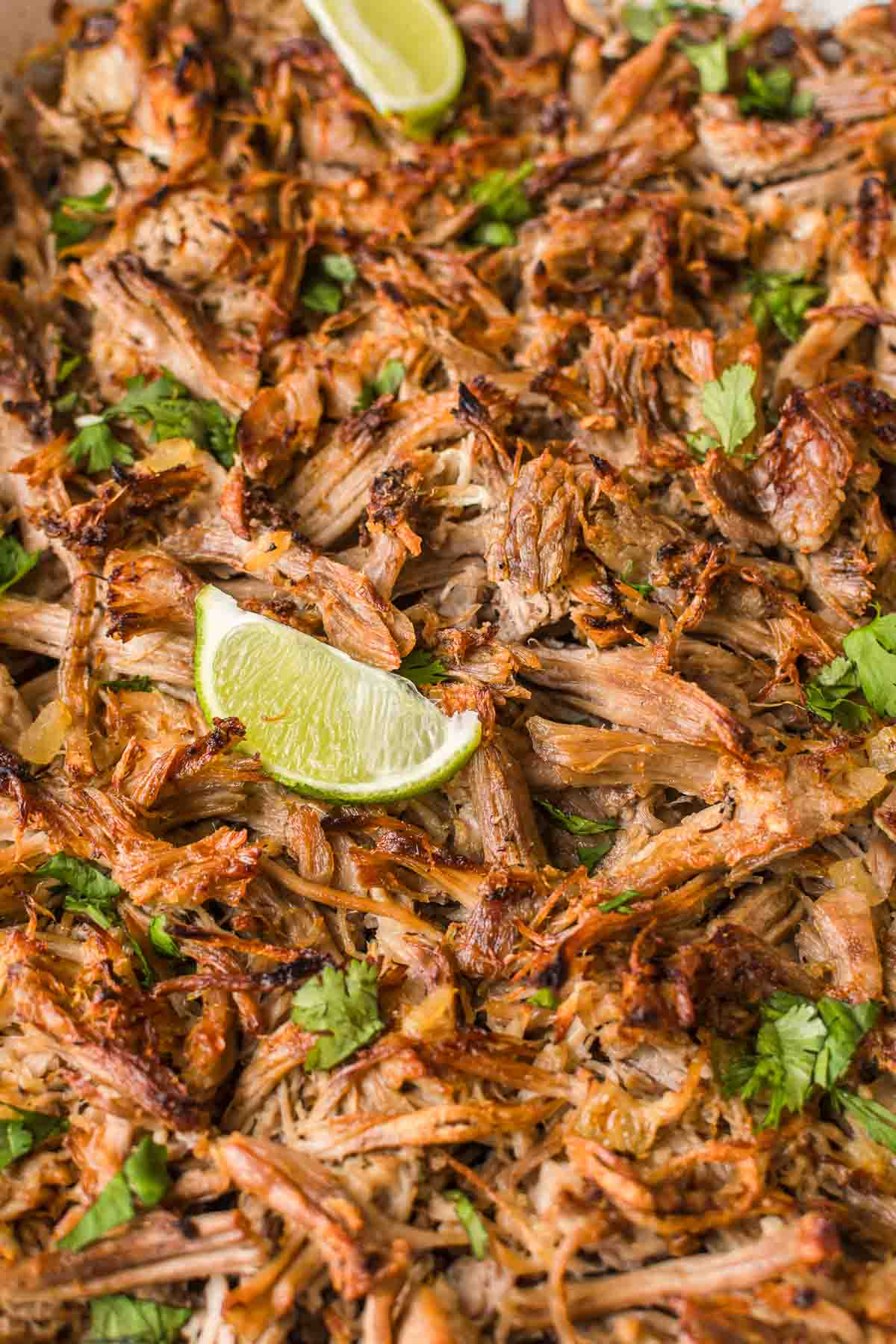 Overhead shot of crispy Carnitas on a baking sheet, with fresh cilantro and lime wedges.