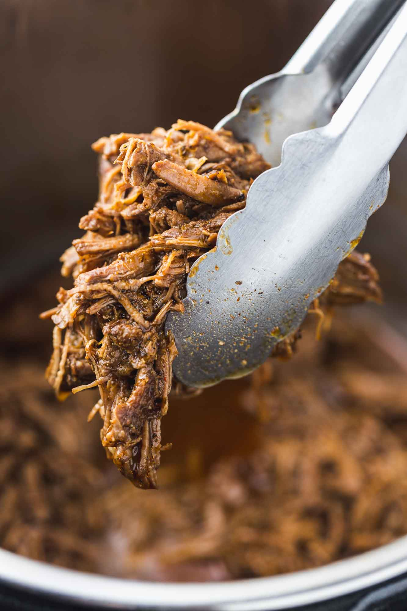 Taking a portion of shredded beef using kitchen tongs