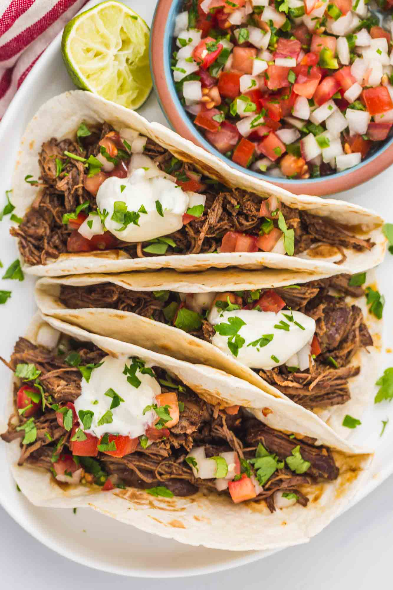 Overhead shot of shredded beef tacos with pico de gallo and lime crema