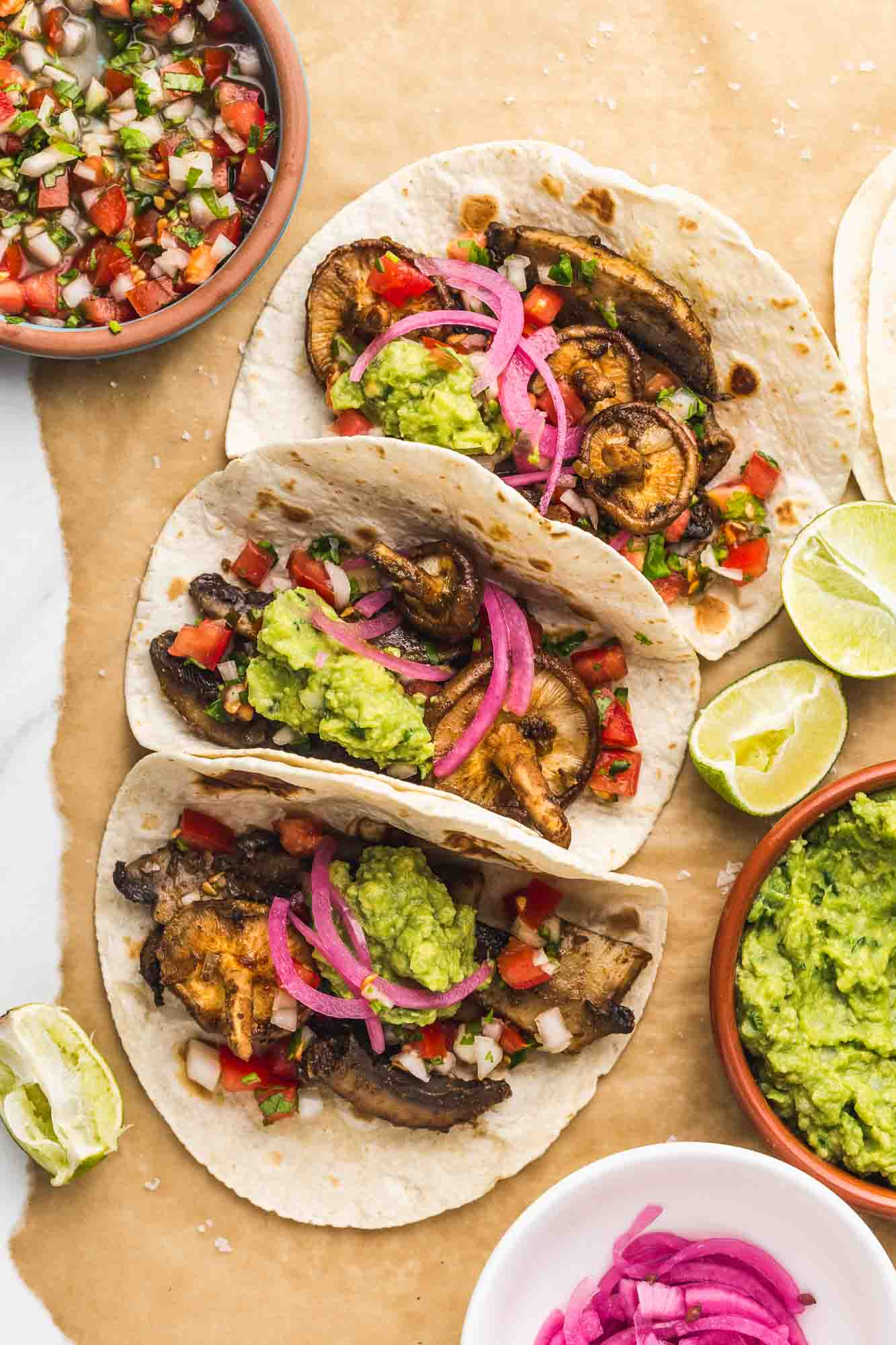 3 mushroom tacos with wedges of lime, guacamole, pico de gallo, and quick pickled onions.