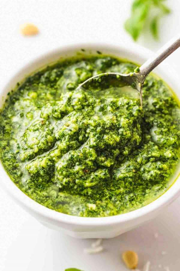 A white bowl with pesto and spoon