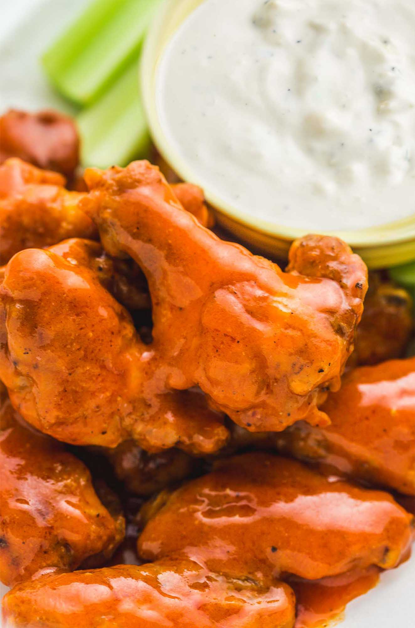 Saucy buffalo chicken wings with blue cheese dip in the background