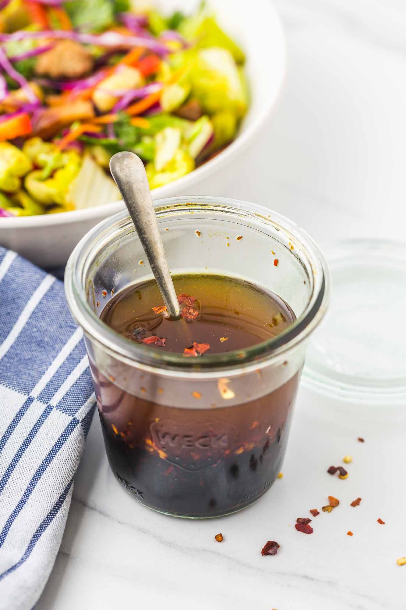 Soy based dressing in a weck jar with a spoon, and a salad in the background