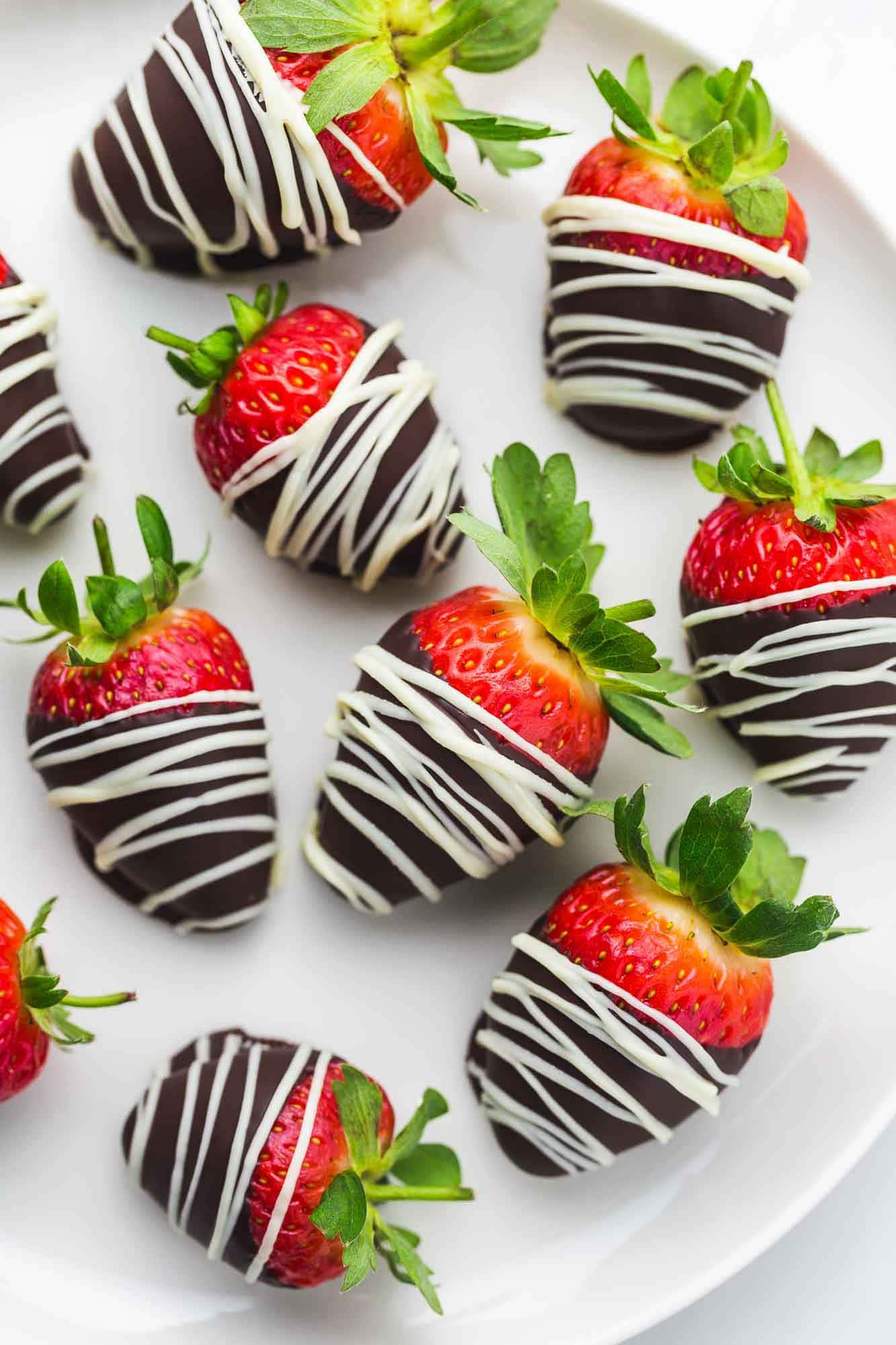 Overhead shot of chocolate covered strawberries with white chocolate drizzle, on a white plate