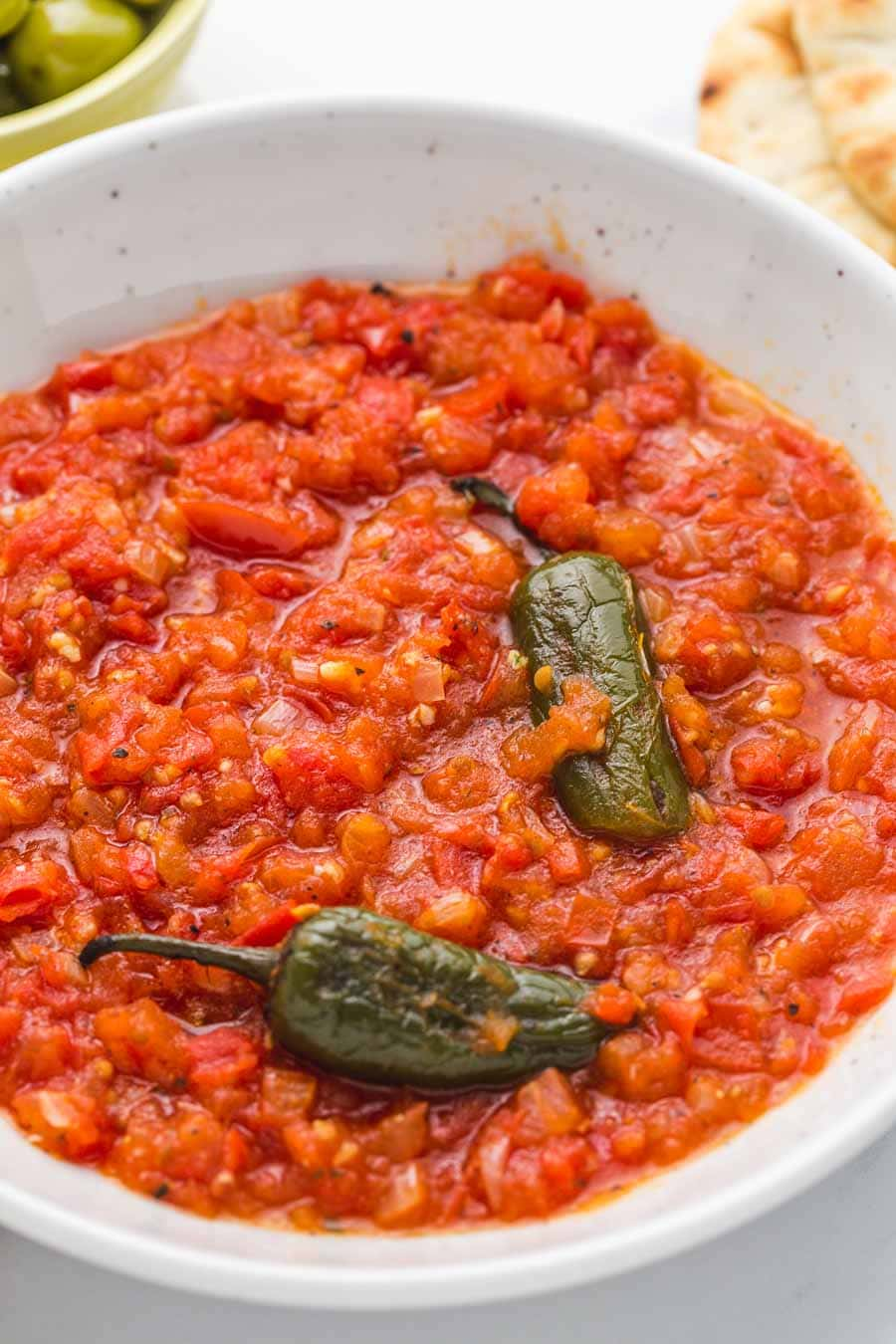 Galayet bandora Jordanian fried tomatoes with jalapeno peppers in a white bowl