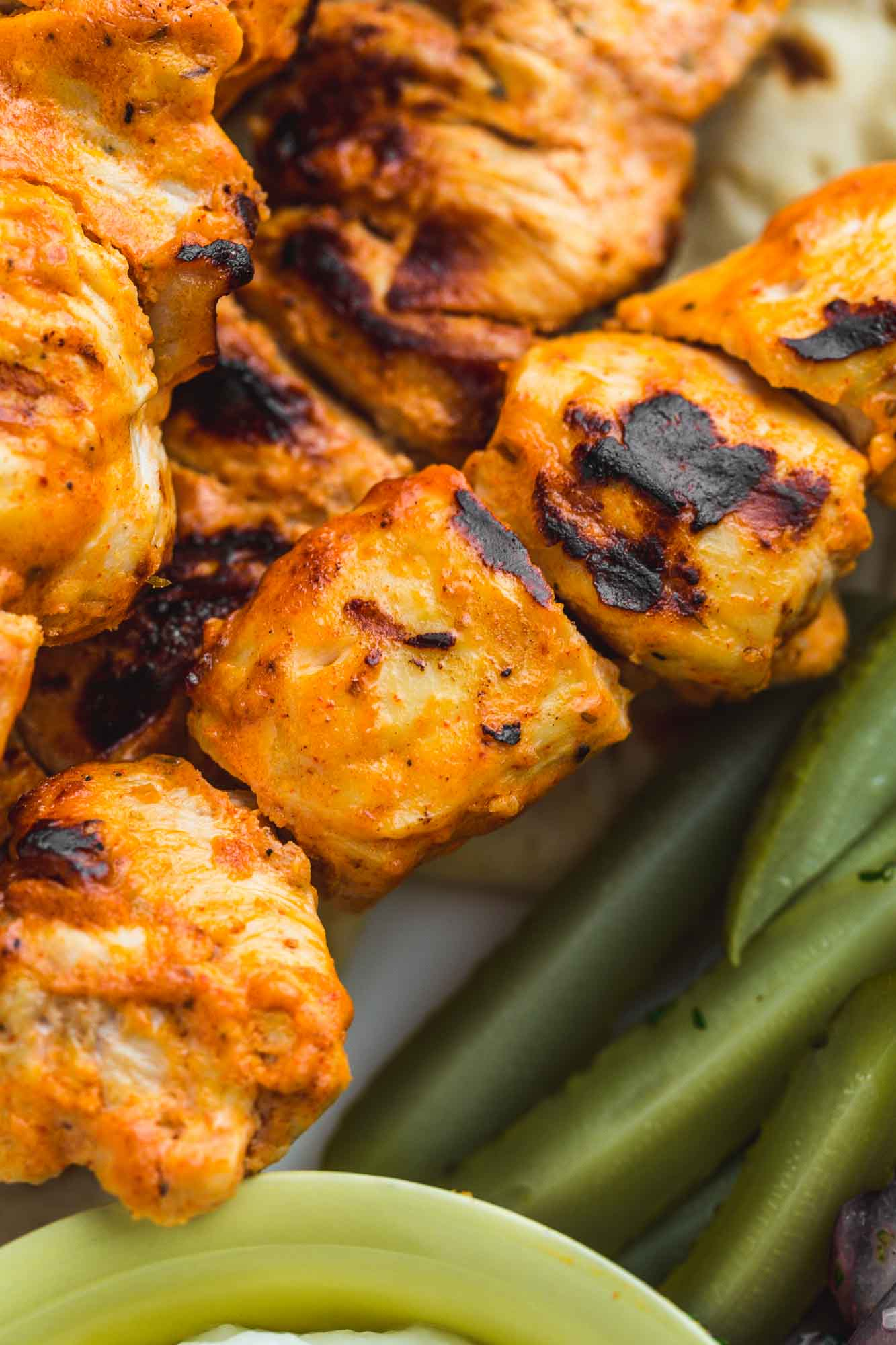 A close up shot of grilled shish tawook chicken on skewers