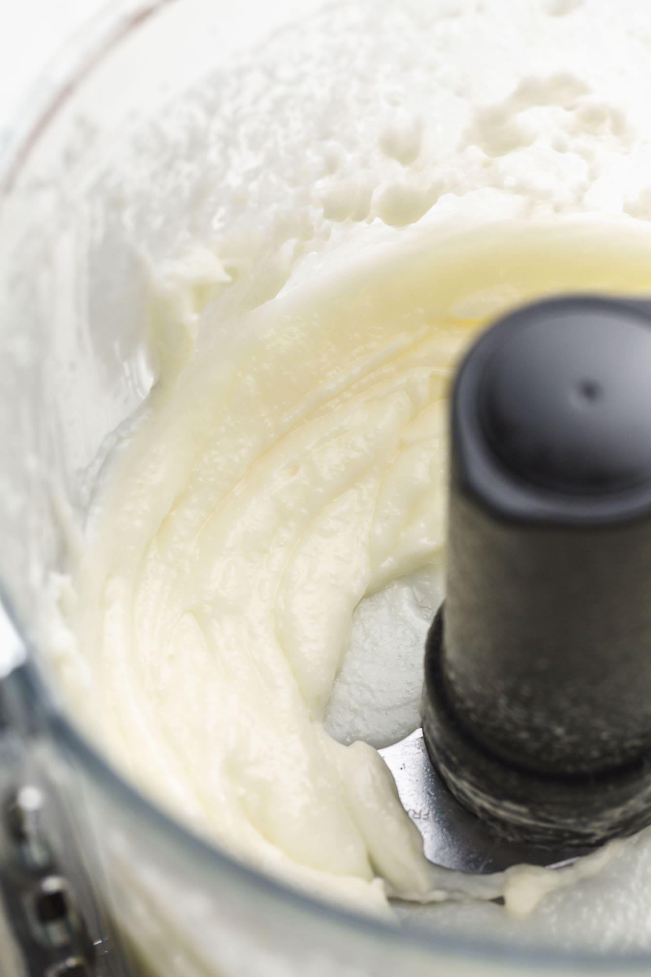 A close up shot of garlic sauce in a food processor bowl