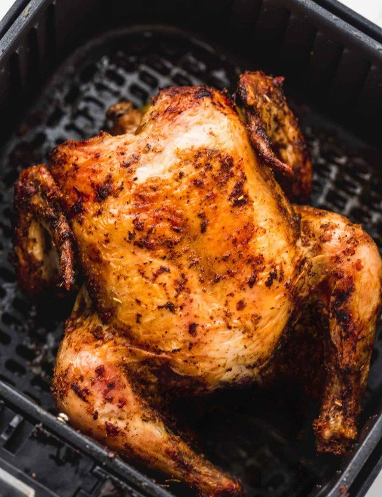 Roasted whole chicken in an air fryer basket