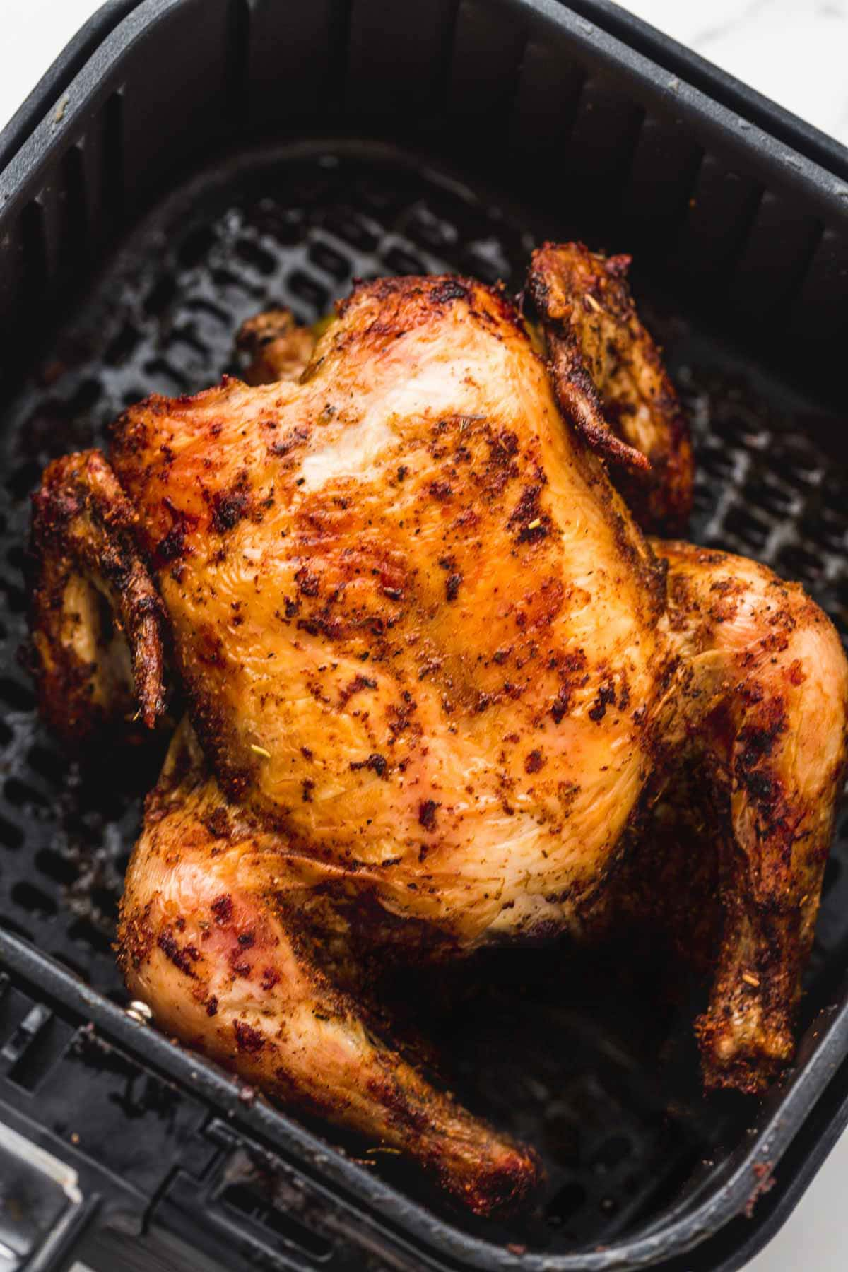 A roasted whole chicken in the air fryer basket