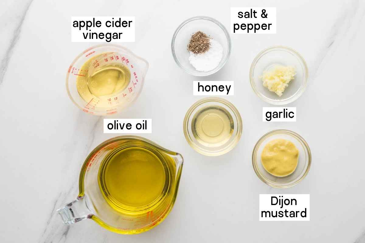 Ingredients needed to make apple cider vinaigrette including apple cider vinegar, olive oil, honey, garlic, dijon mustard, salt and pepper.