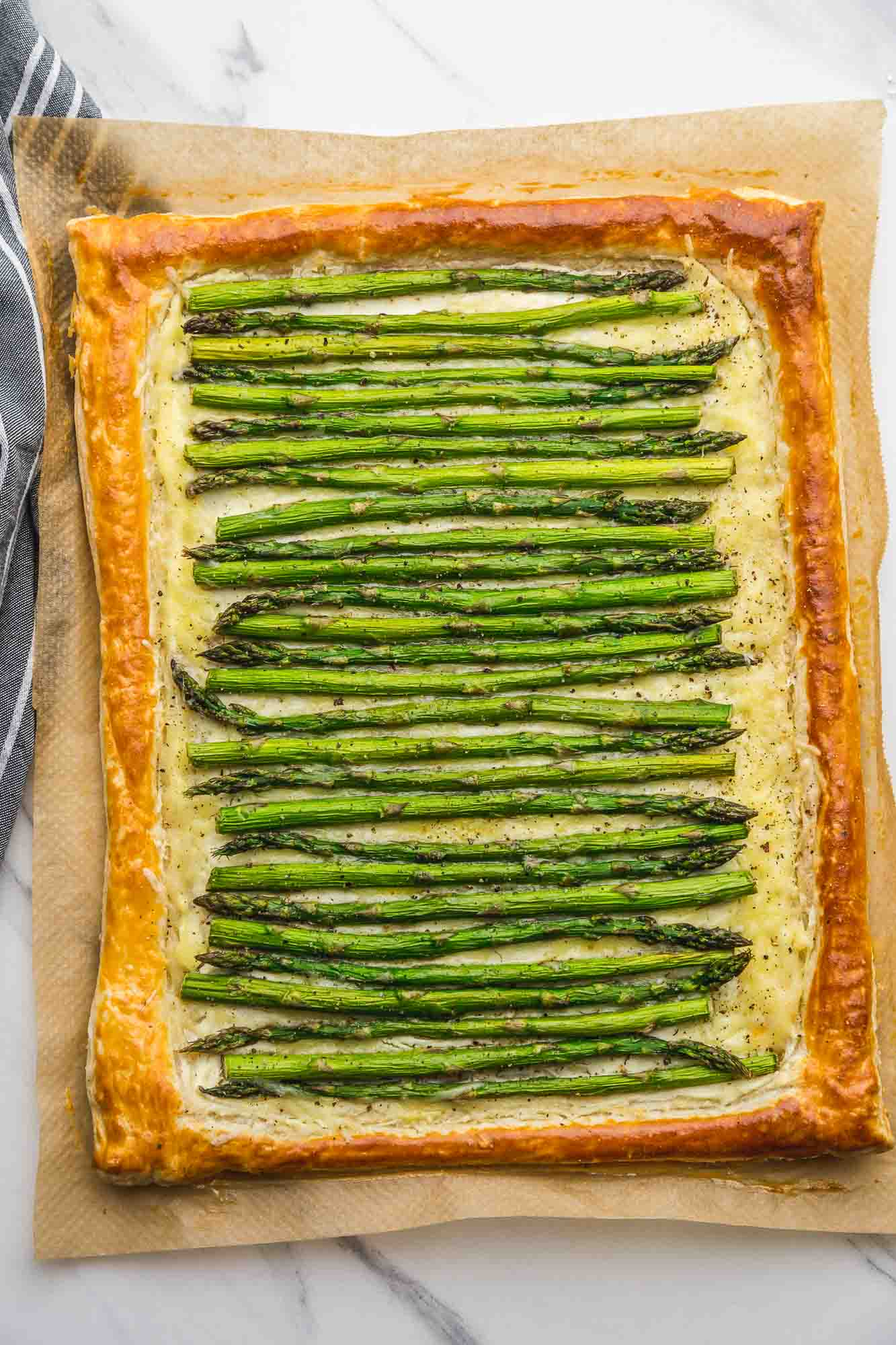 Overhead shot of an asparagus tart over parchment paper and a tea towel.