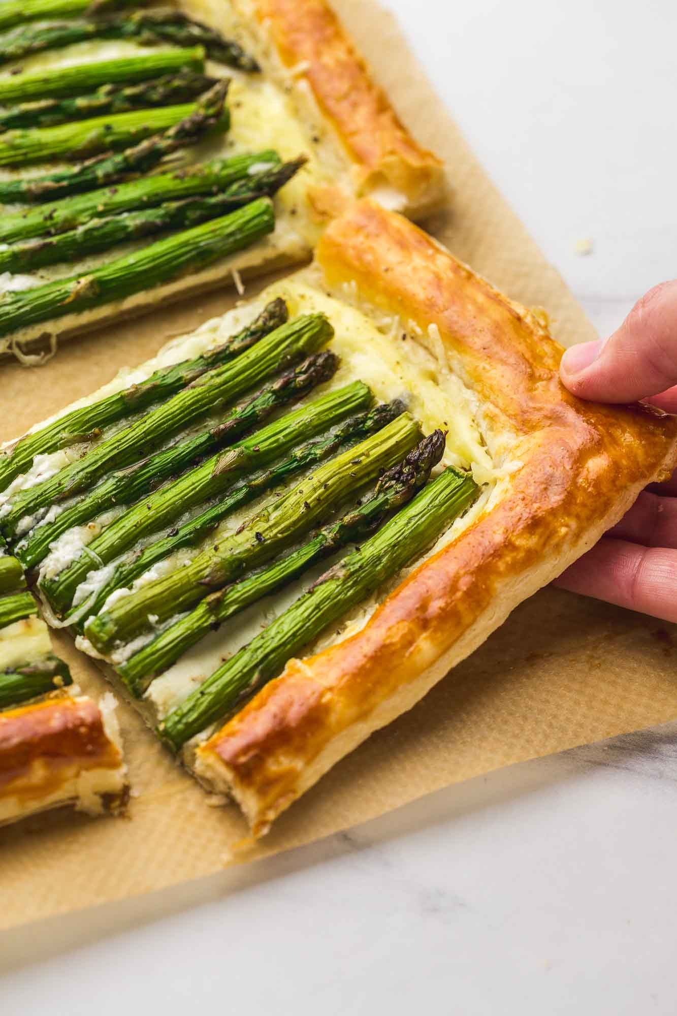 An asparagus tart square and a hand in motion