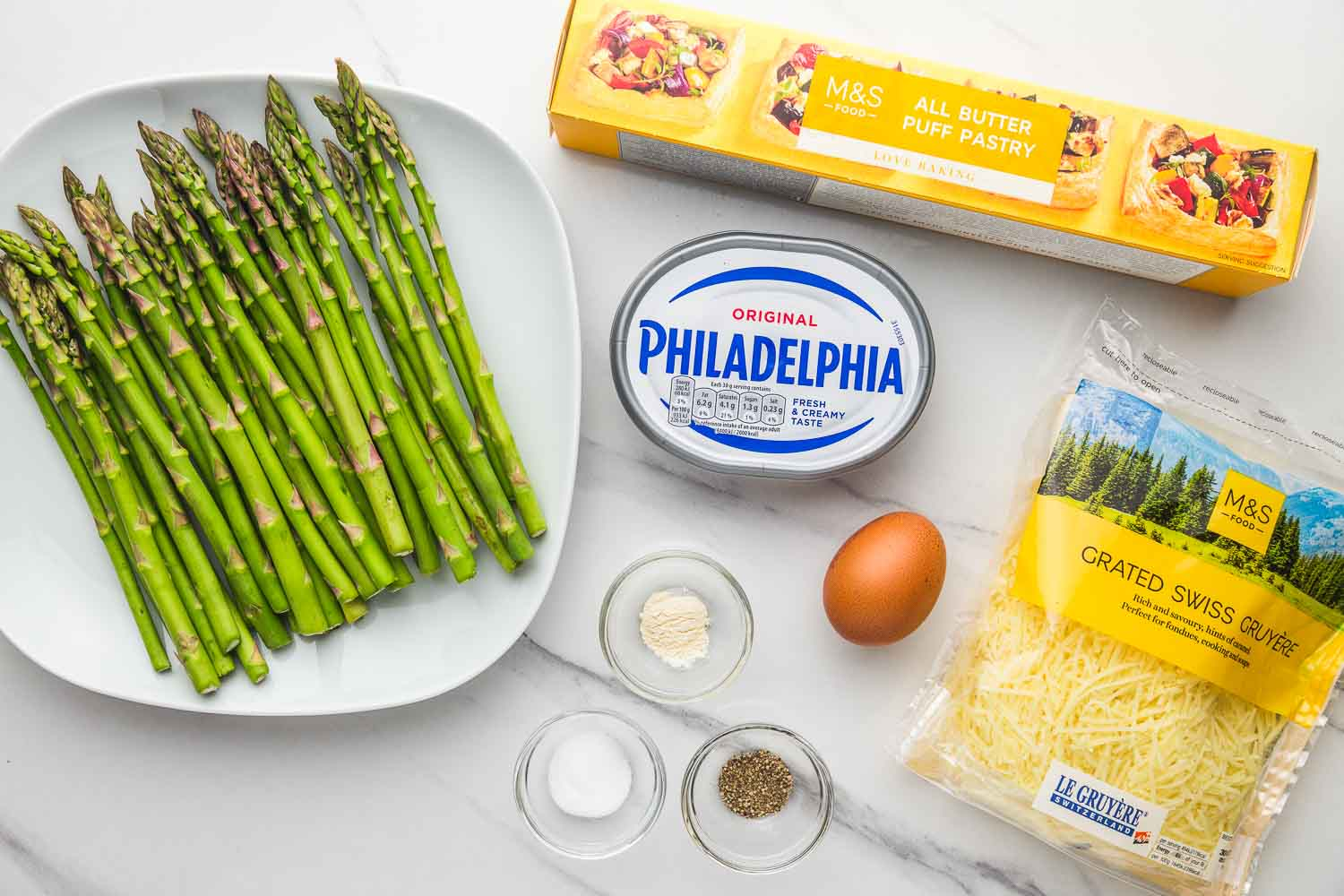 Ingredients needed for asparagus tart: fresh asparagus spears, all butter puff pastry, philadelphia cream cheese, grated swiss gruyere cheese, an egg for an egg wash, and seasonings.