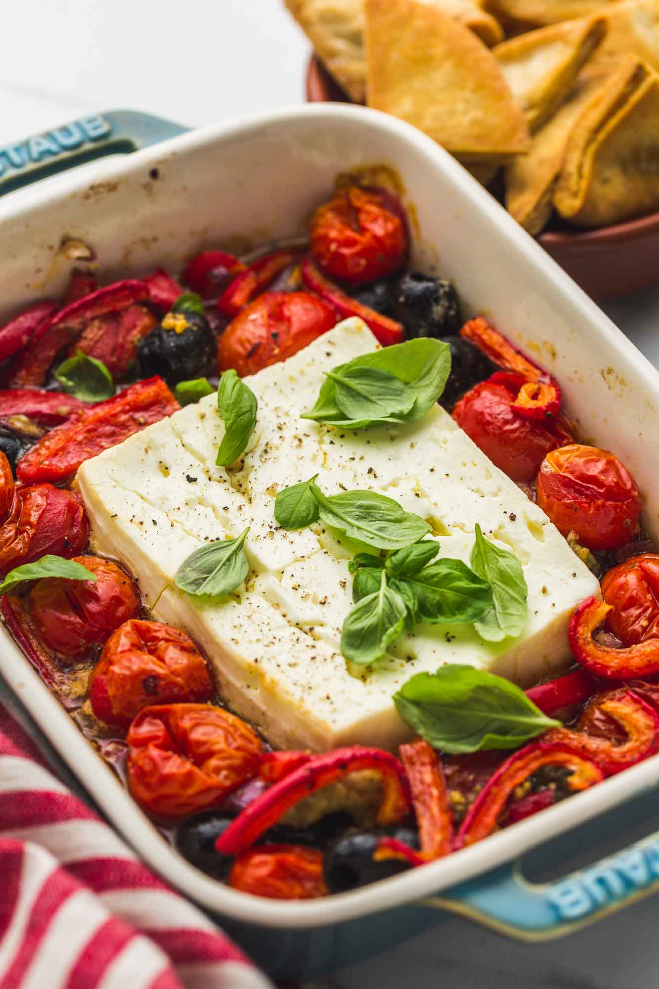 Baked feta dip with roasted vegetables in a blue Staub baking dish, garnished with fresh basil leaves.