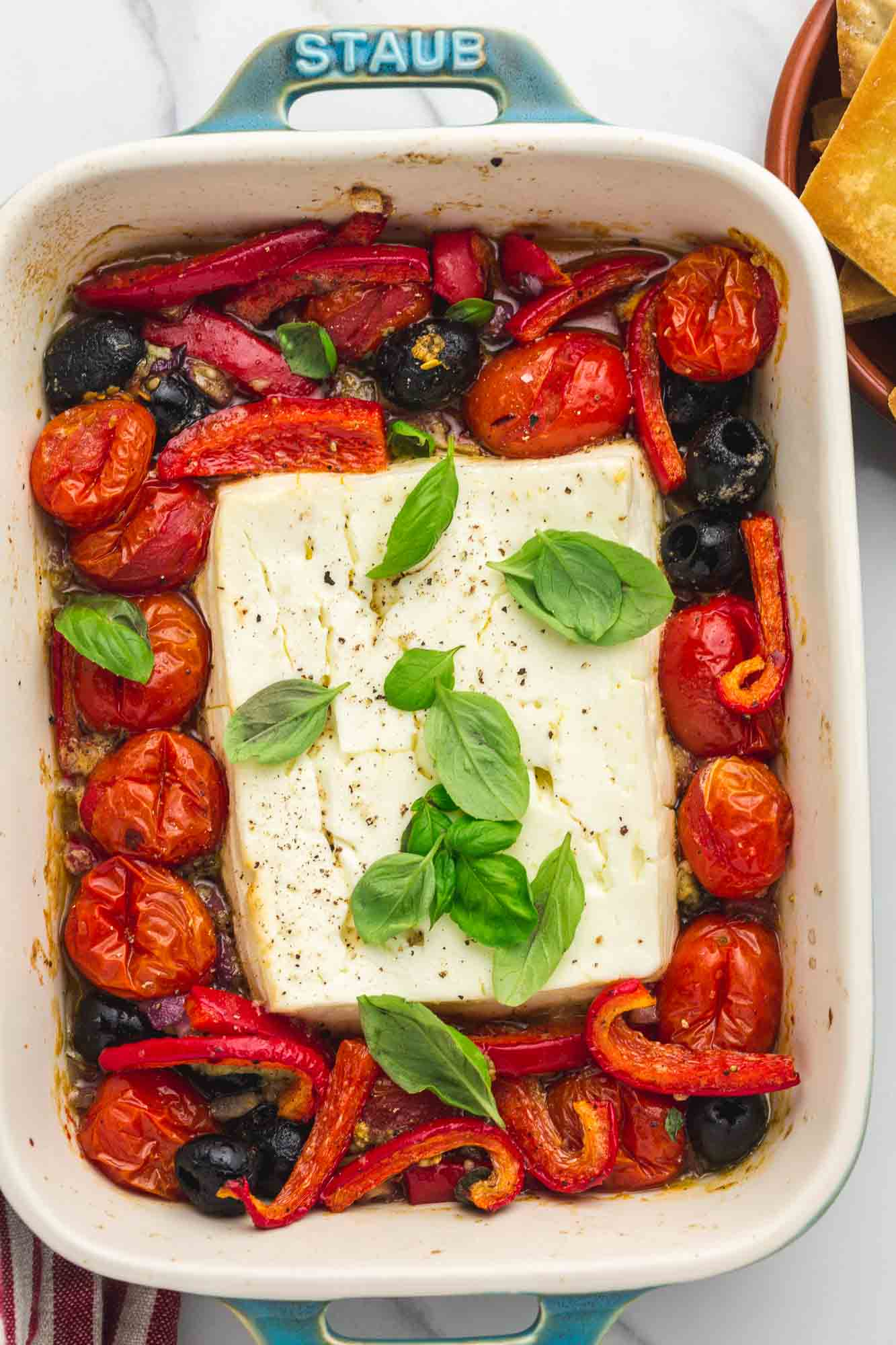 Baked feta dip with roasted vegetables in a baking dish, garnished with fresh basil leaves.