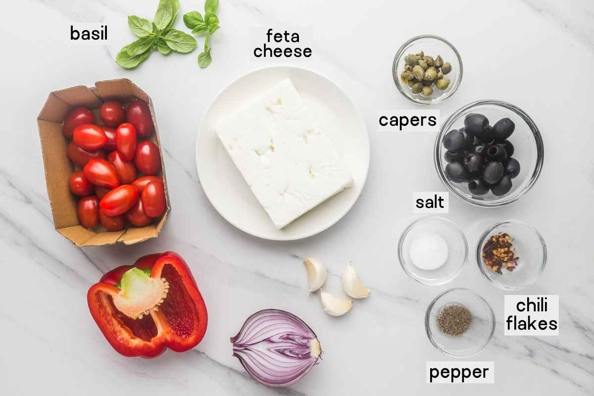 Ingredients needed to make the baked feta dip including feta, cherry tomatoes, onion, bell pepper, capeers, olives, salt, pepper, chili flakes, and basil leaves.