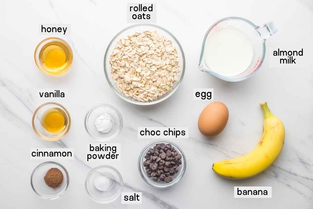 Ingredients needed to make baked oats: rolled oats, almond milk, banana, egg, baking powder, honey, cinnamon, vanilla, salt, and chocolate chips.