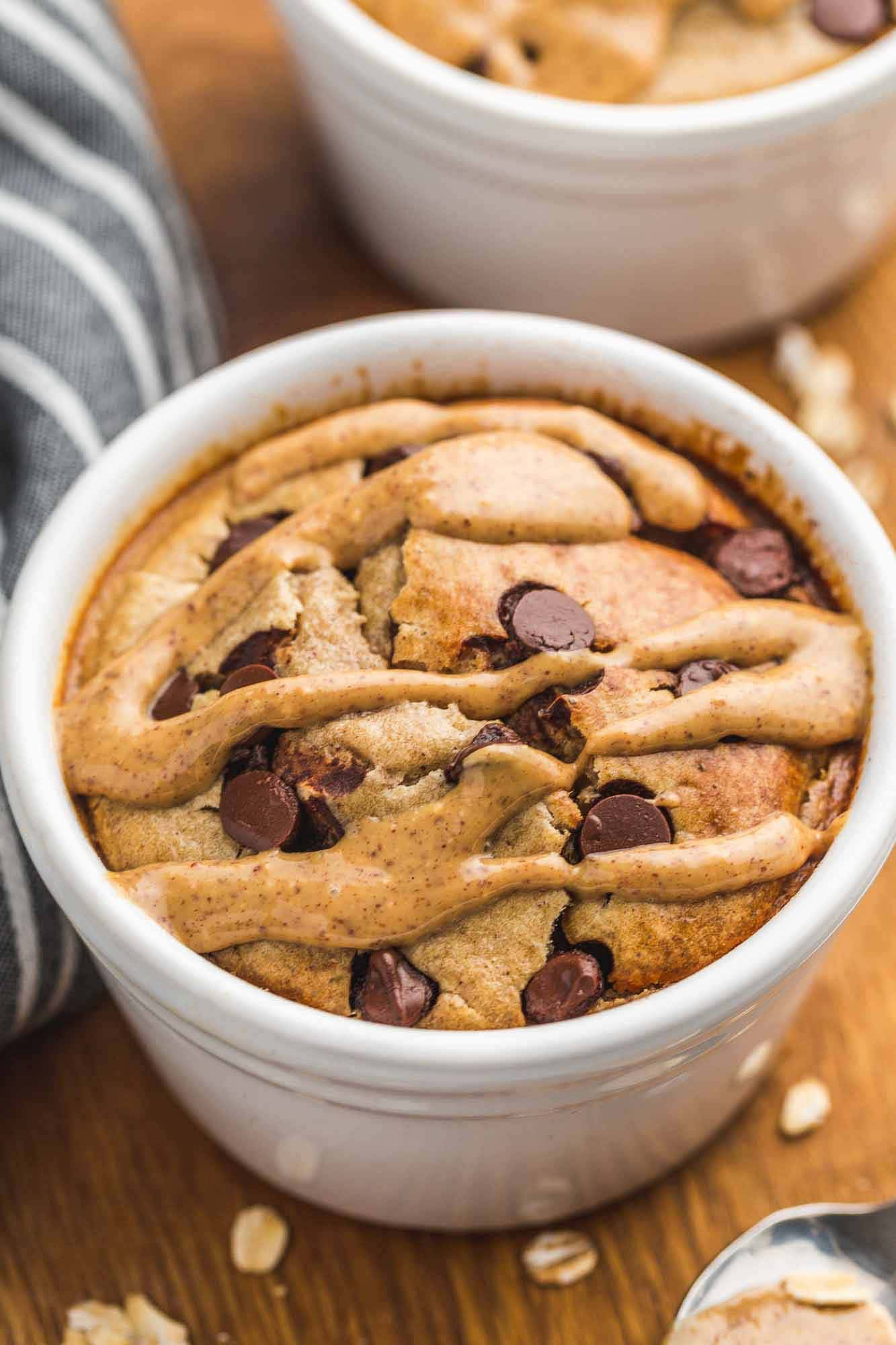 Baked Oats in white ramekin with chocolate chips, and a drizzle of peanut butter.