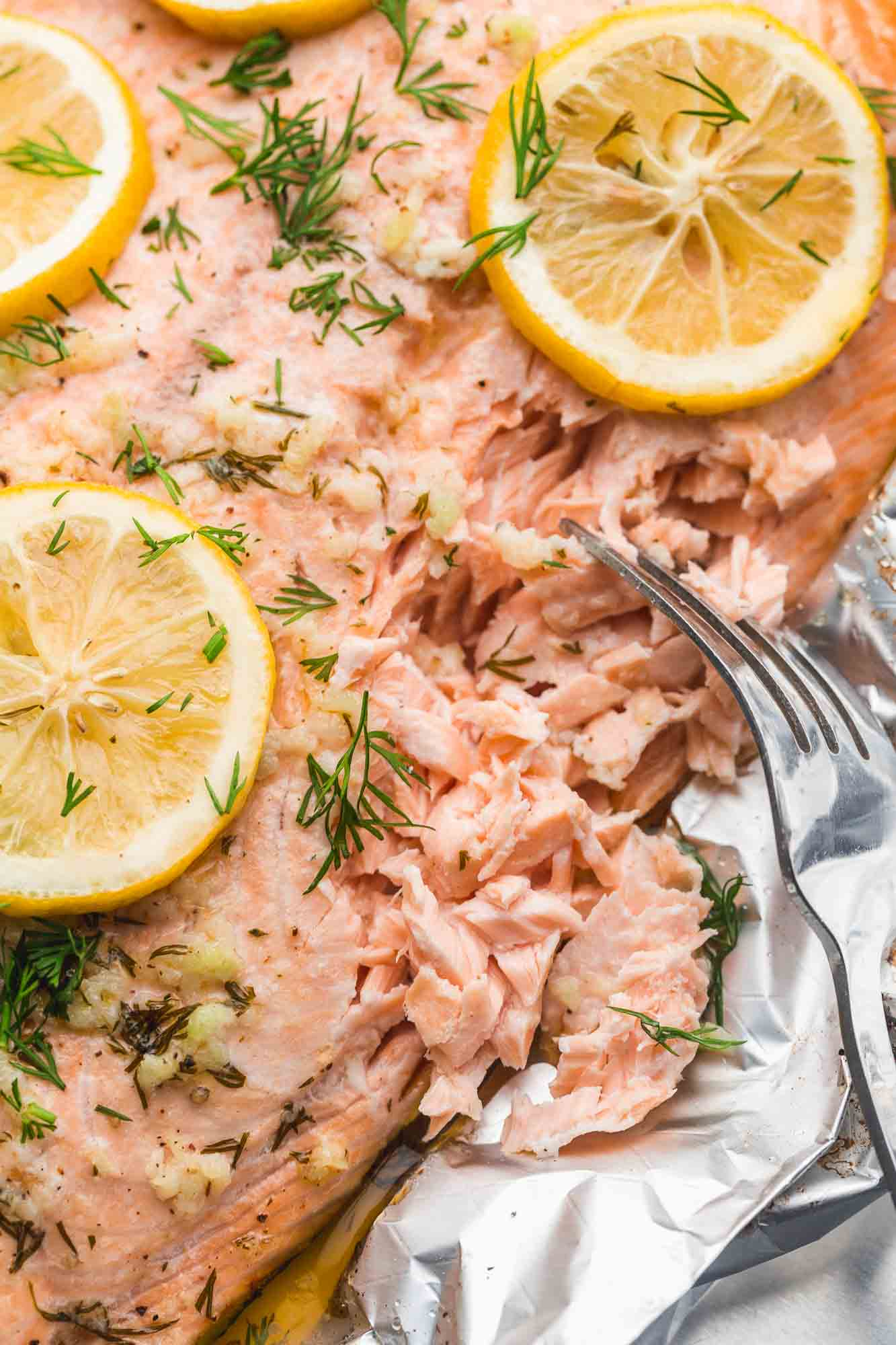 Whole side of salmon baked in foil flaked with a fork. With lemon slices and fresh dill.