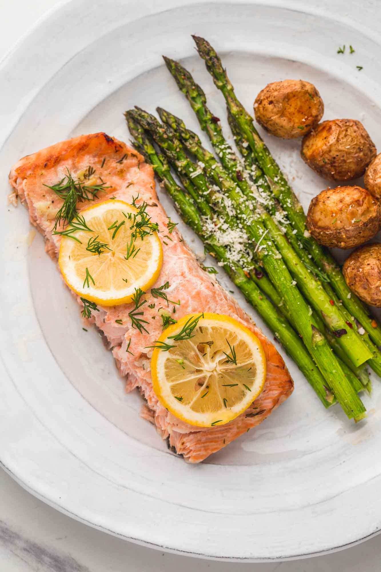 A slice of baked salmon served with roasted asparagus and roasted potatoes.