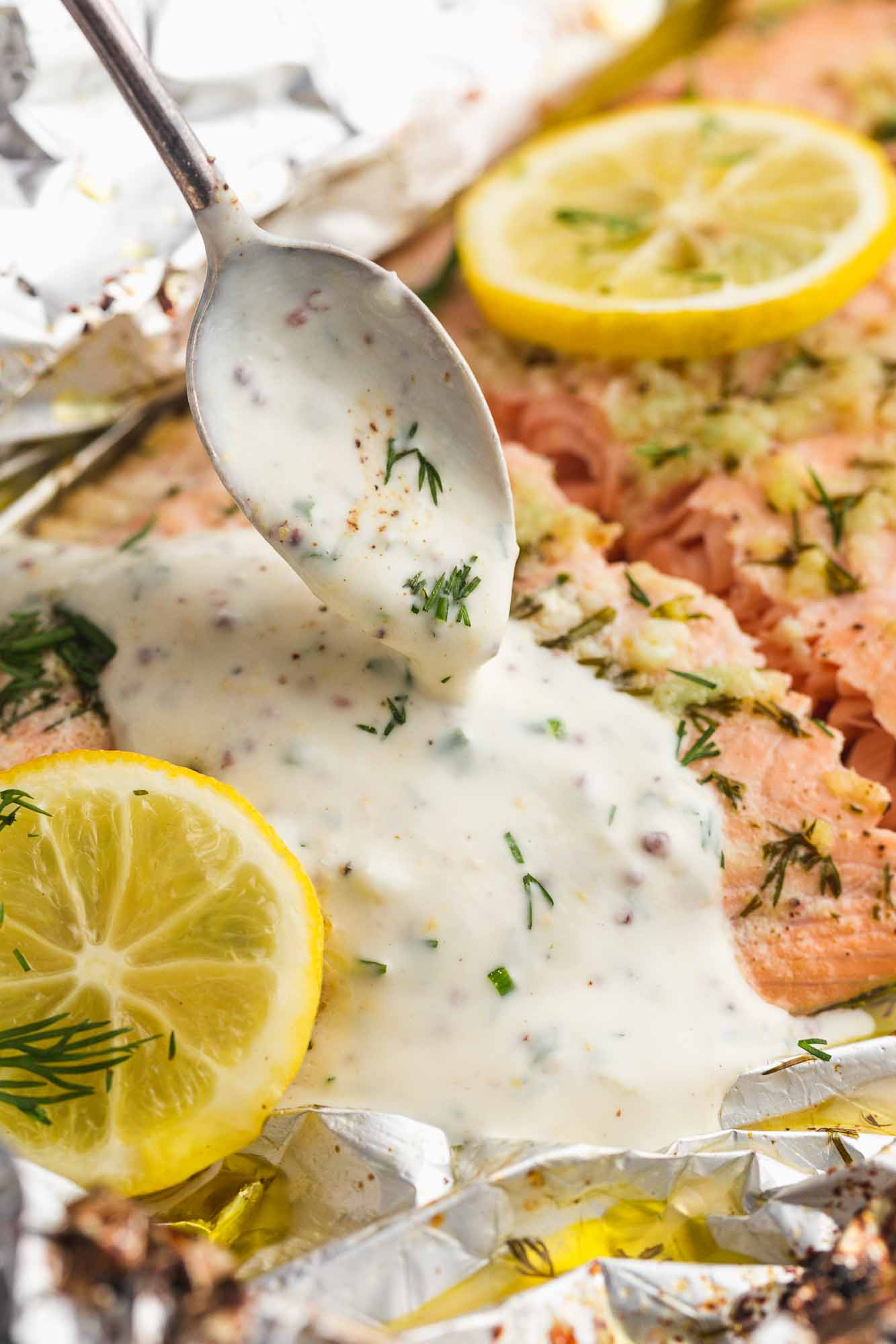 Drizzling herb cream sauce over baked salmon with a spoon.