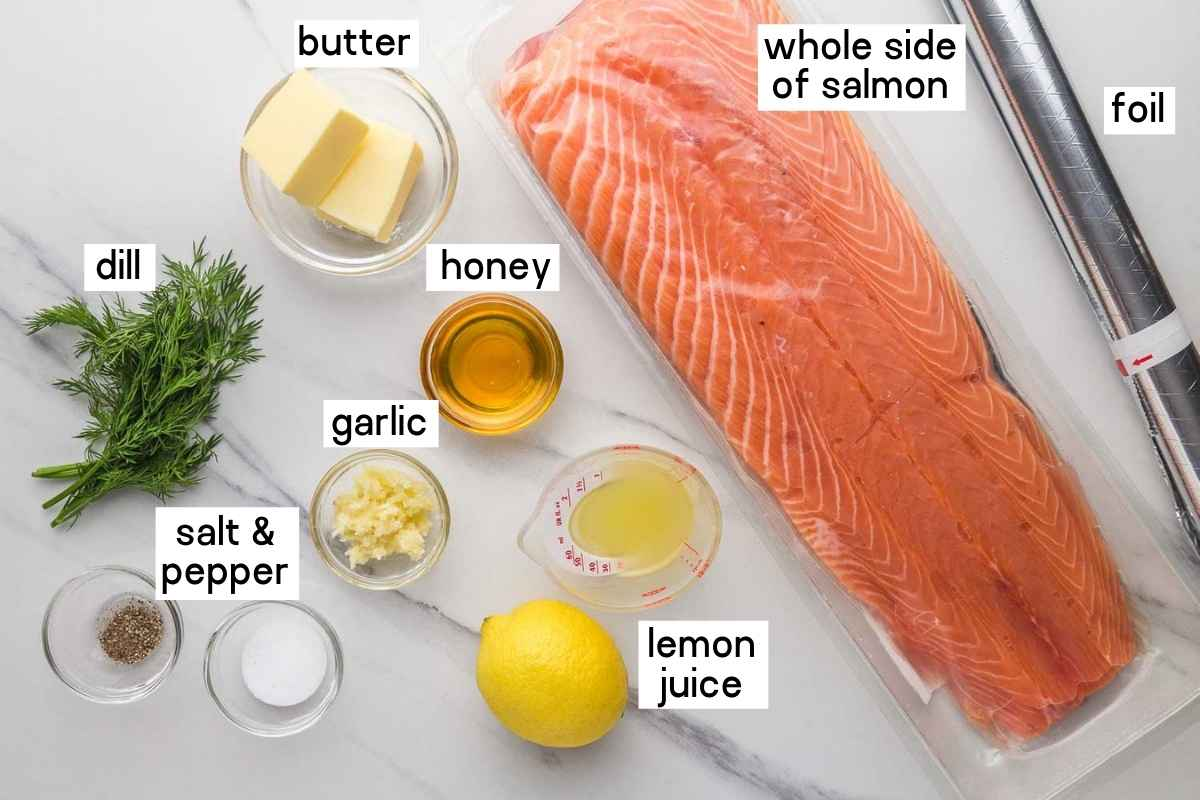 Ingredients needed to bake salmon in foil: whole side of salmon, butter, honey, garlic, lemon juice, dill, salt and pepper. And foil.