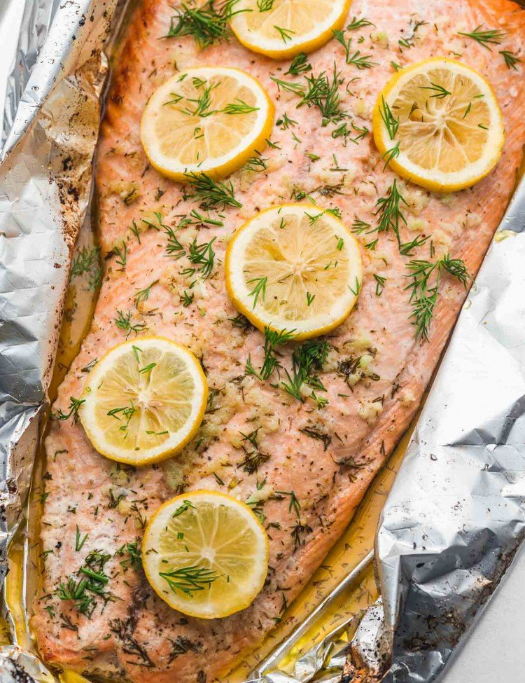 Whole side of salmon baked in foil, with lemon slices and fresh herbs.
