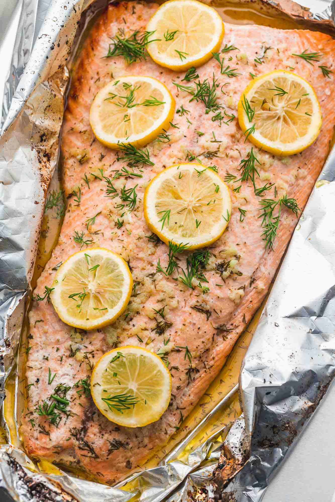 Whole side of salmon baked in foil with lemon slices, garlic butter, and dill.