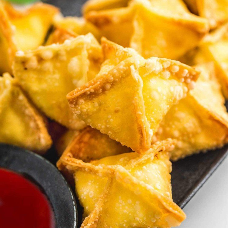 Cream cheese rangoons on a platter with sweet and sour dipping sauce