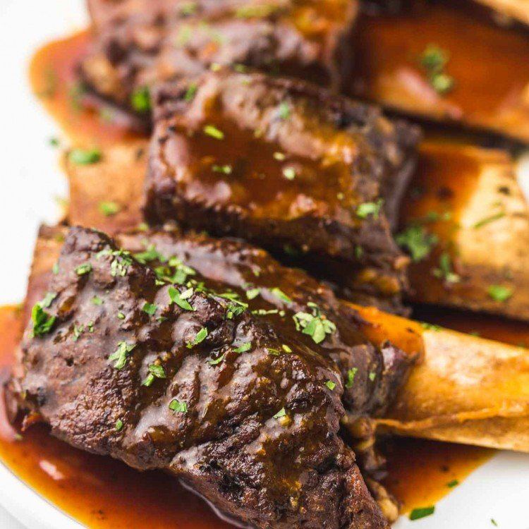 Short ribs in sauce served on a white platter