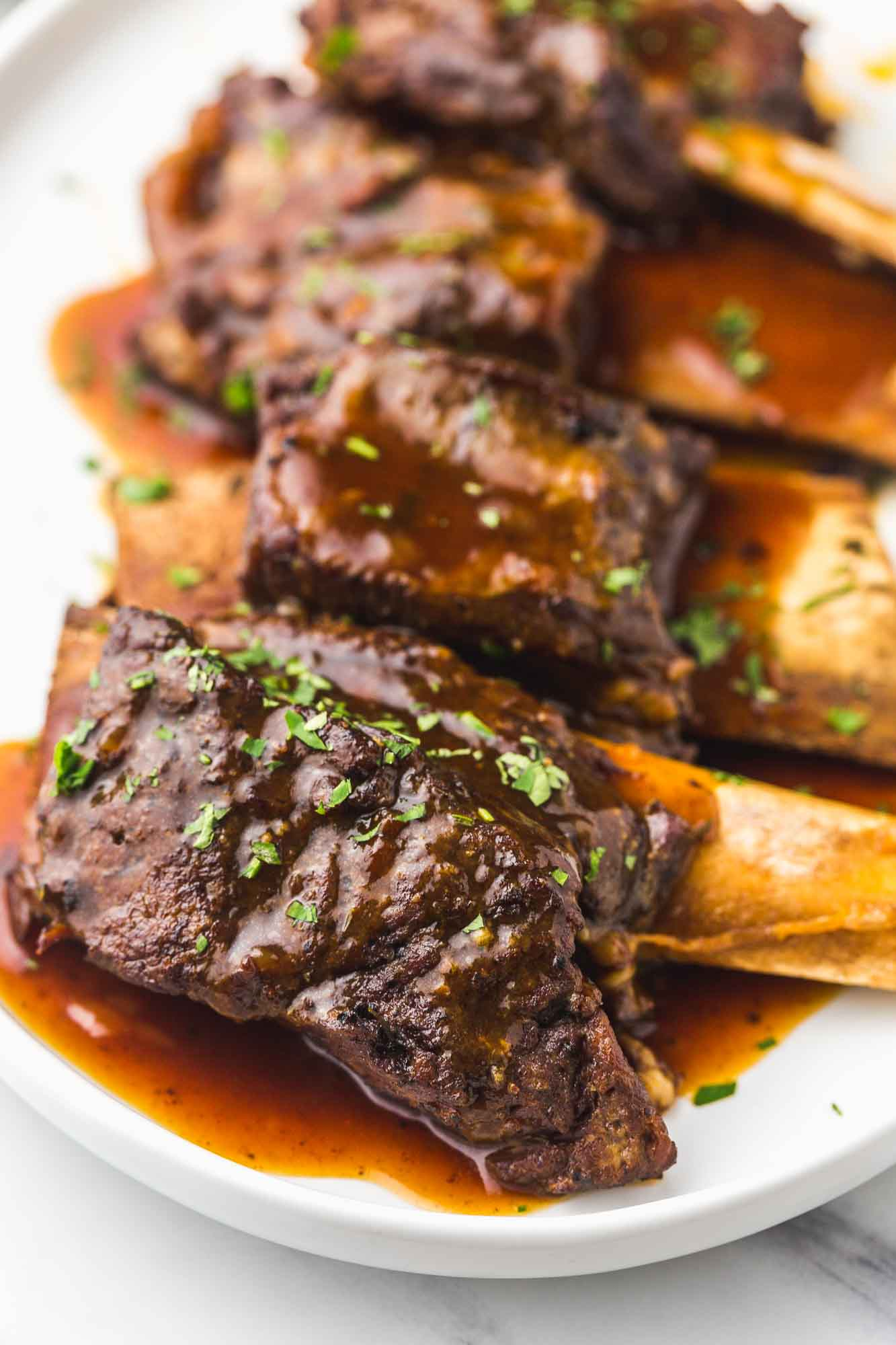 Braised short ribs on a platter, garnished with fresh parsley.