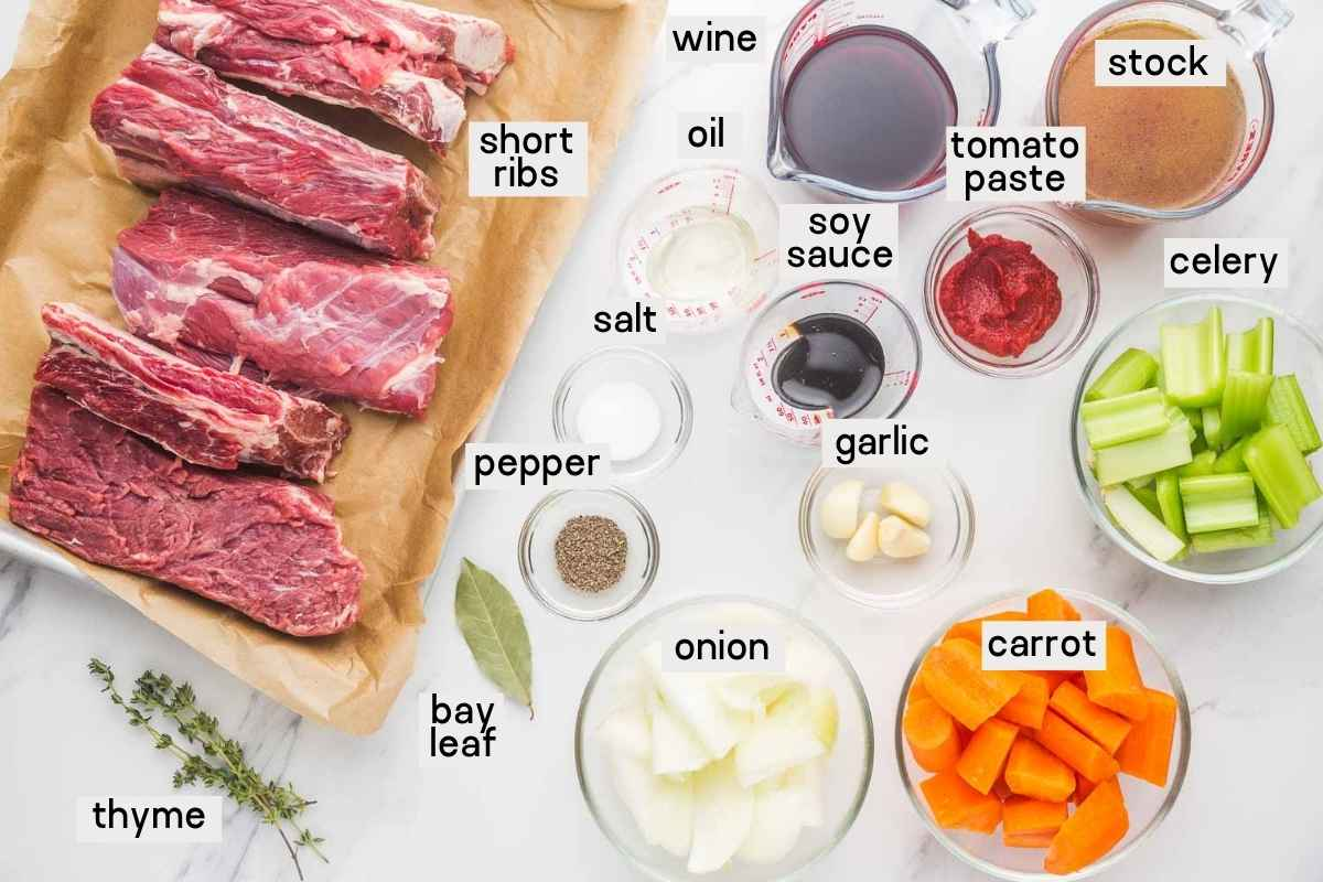 Ingredients needed for Instant Pot short ribs, short ribs, wine, stock, tomato paste, soy sauce, celery, carrot, onion, garlic, salt, pepper, bay leaf, and thyme.
