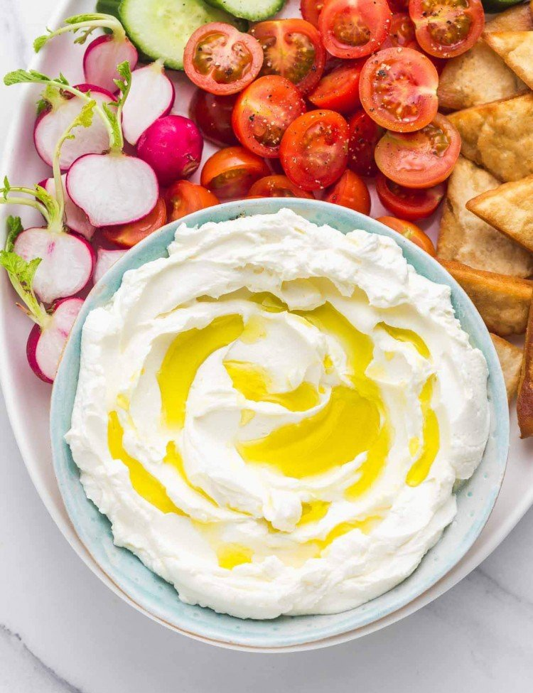 A blue bowl with labneh strained yogurt and crudites in a platter