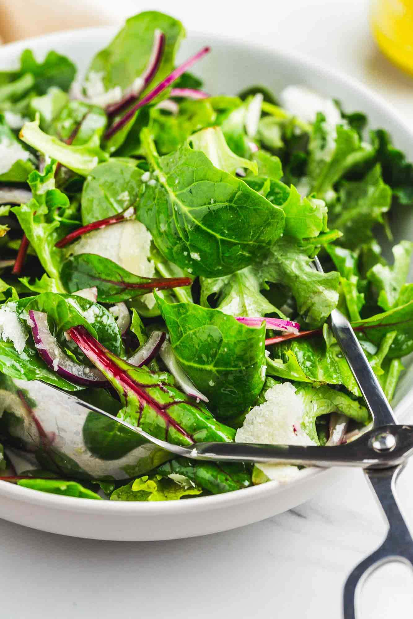 Tossed green salad with parmesan shavings, and a serving spoon