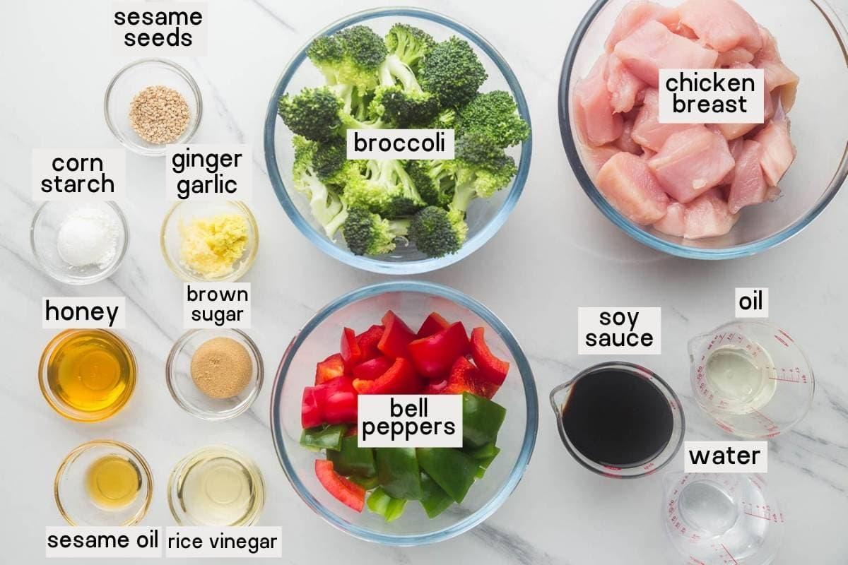 Ingredients needed to make Teriyaki Chicken Stir Fry, includes chicken, broccoli, bell peppers, soy sauce, oil, water, cornstarch, ginger, garlic, honey, brown sugar, sesame oil, rice vinegar and sesame seeds.