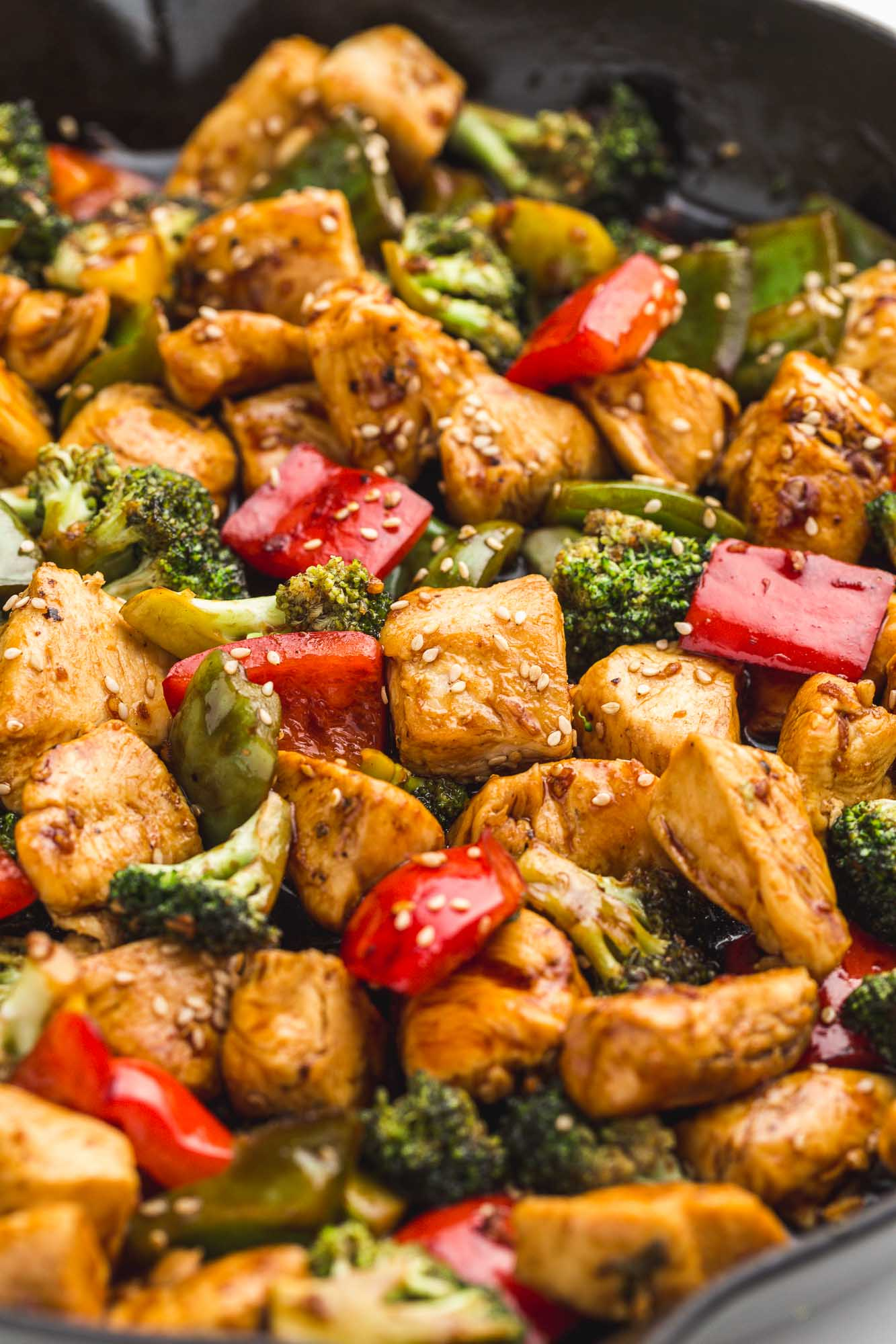 An angle shot of teriyaki chicken stir fry in a cast iron skillet.