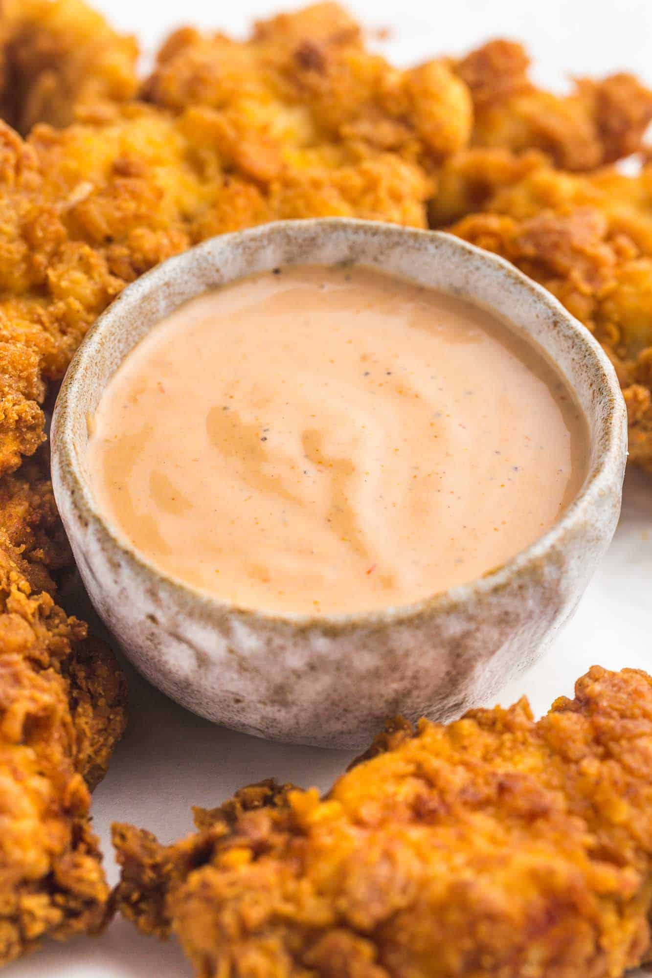 A small bowl with Cane's dipping sauce, and fried chicken tenders on the side