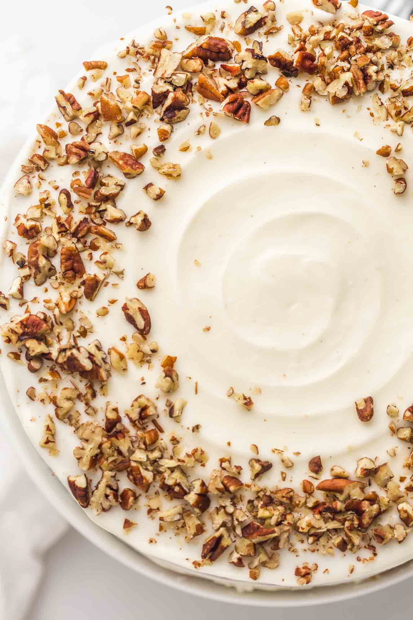 Overhead shot of the carrot cake with cream cheese frosting and crushed pecans.