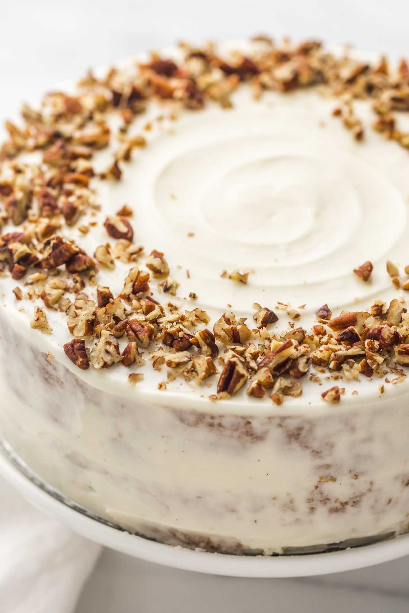 Side view of the gluten free carrot cake with cream cheese frosting and crushed pecans.