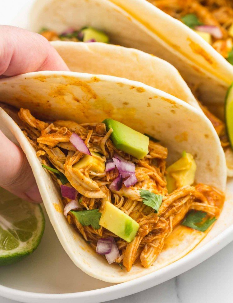 Holding a chicken tinga taco with fresh avocado and finely diced red onion