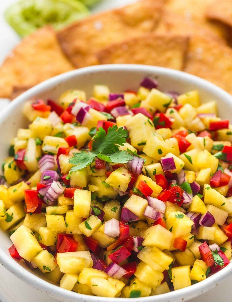 Pineapple salsa served in a white speckled bowl with tortilla chips in the background
