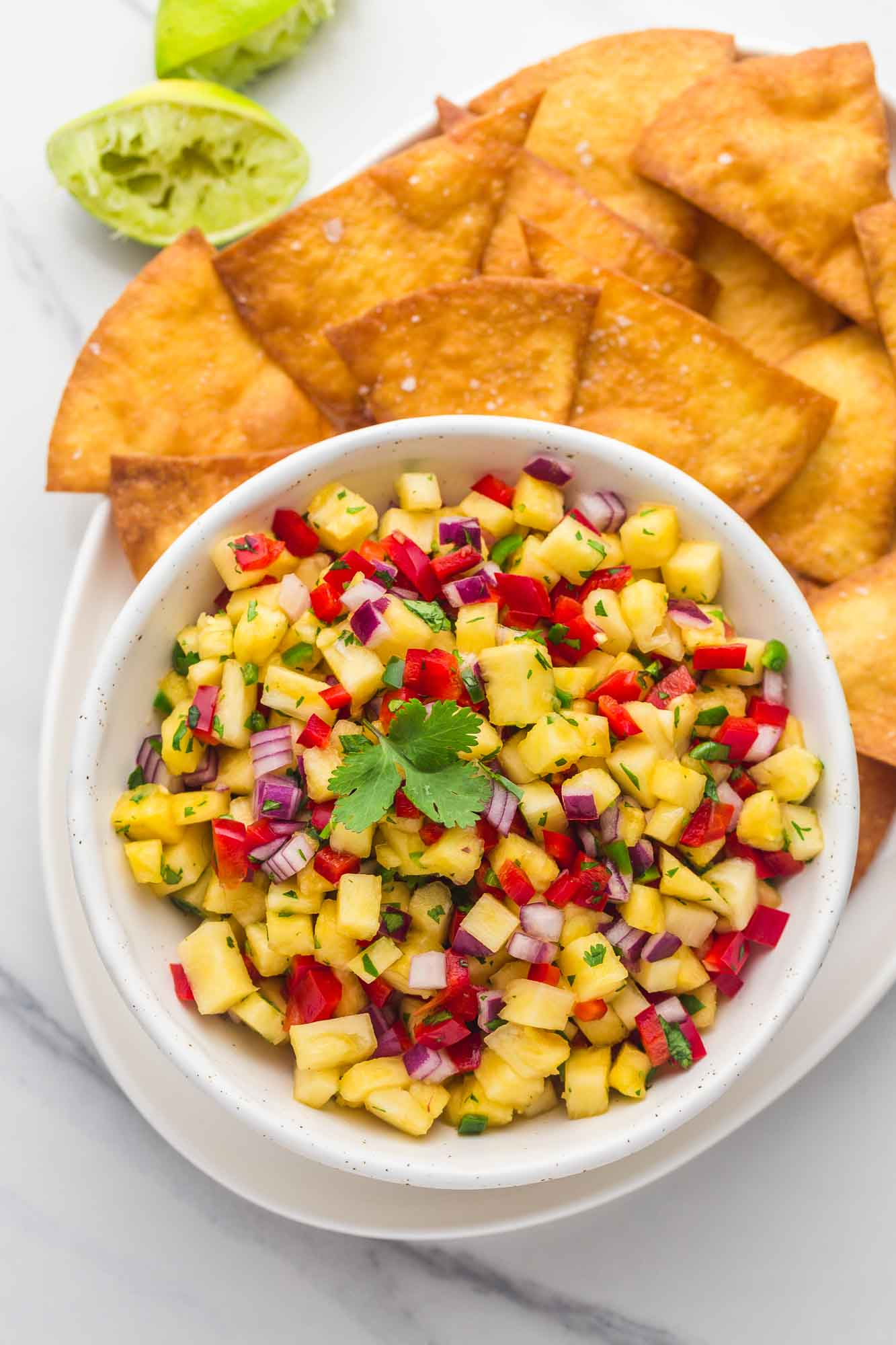 A platter with a bowl of pineapple salsa with tortilla chips