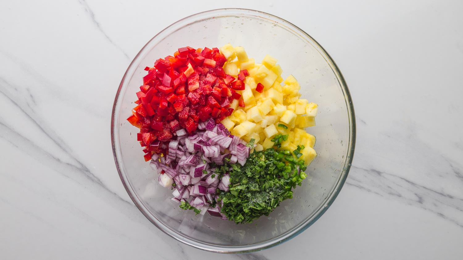 Chopped ingredients for pineapple salsa in a glass bowl