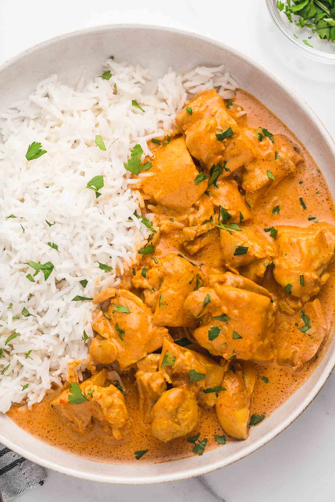 Butter chicken and rice served in a white bowl