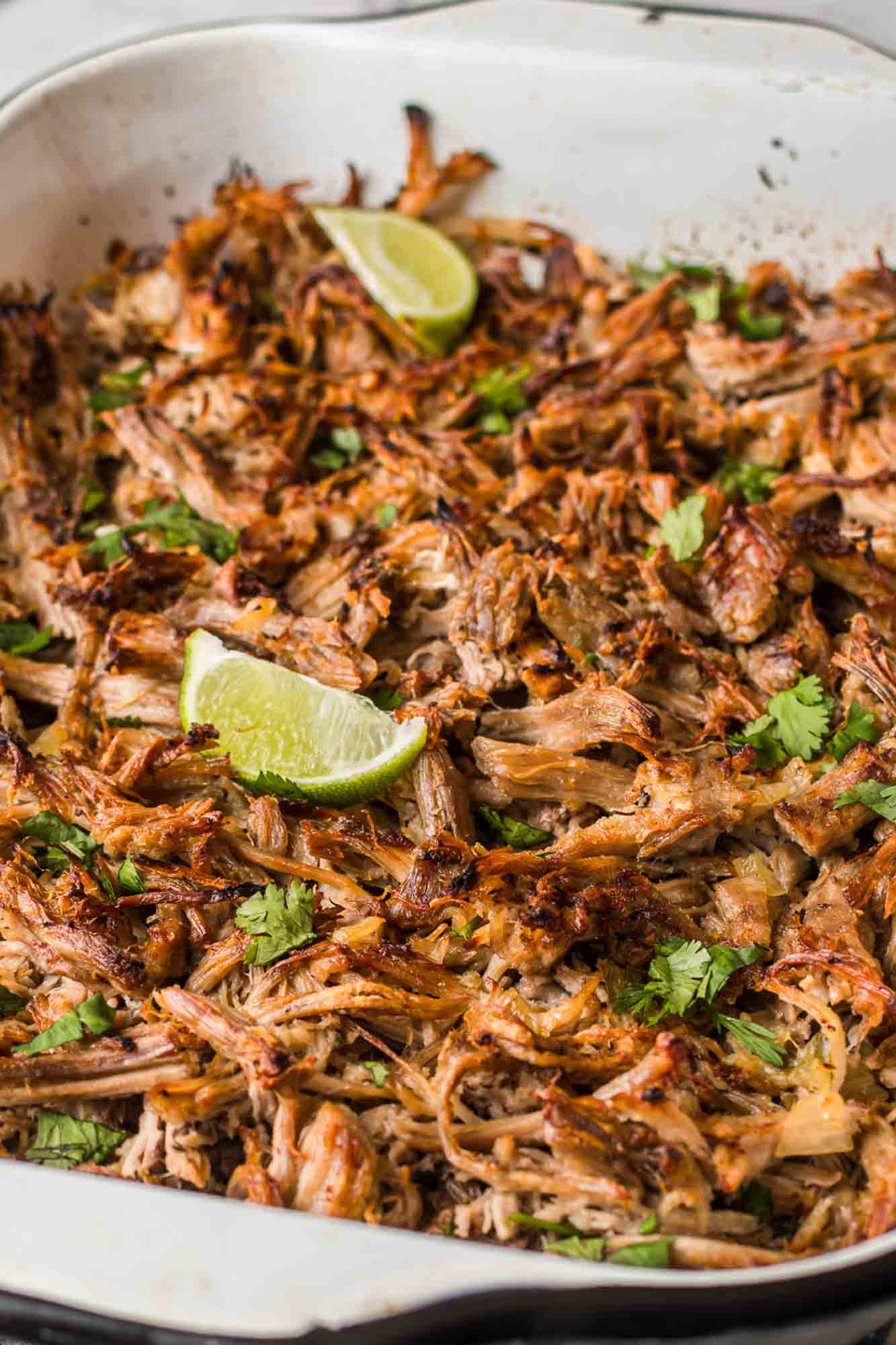Crispy shredded carnitas in a pan with lime wedges and fresh cilantro