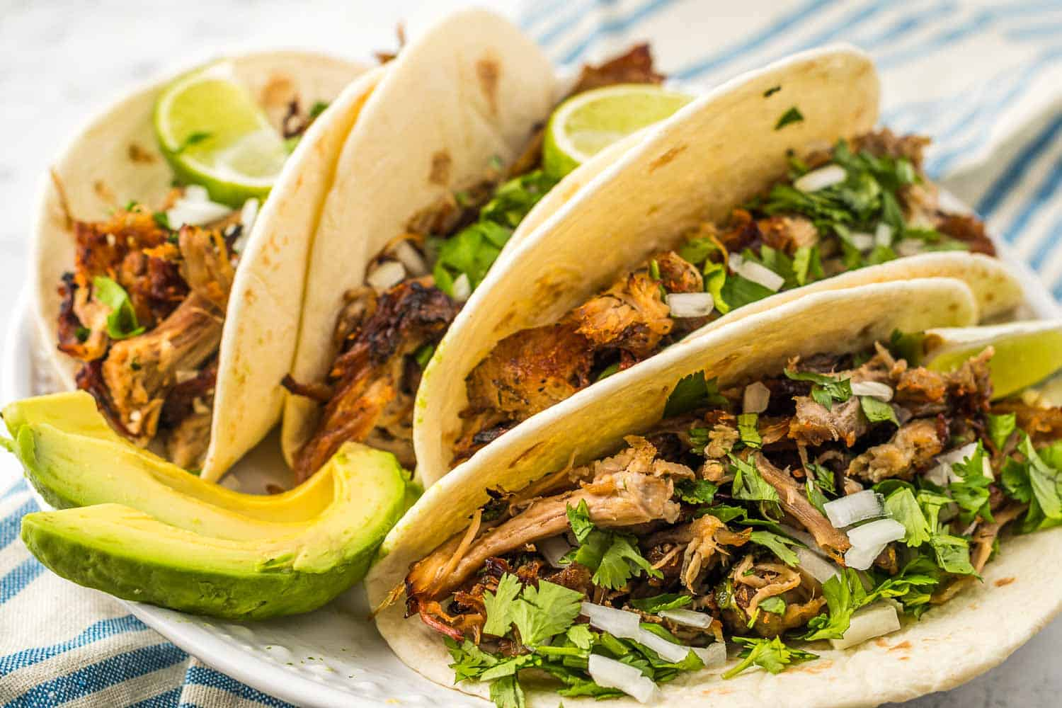 Carnita tacos on a platter with fresh sliced avocago