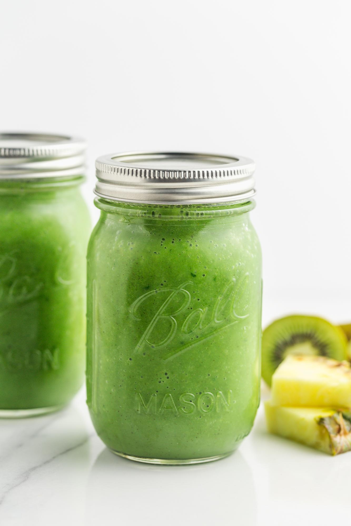 2 sealed mason jars filled with green smoothie
