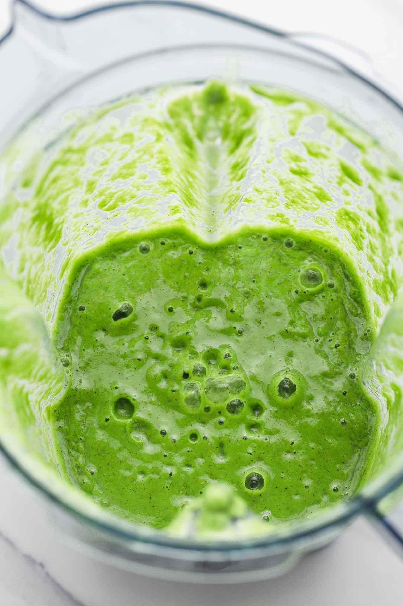 Blender jug filled with green smoothie