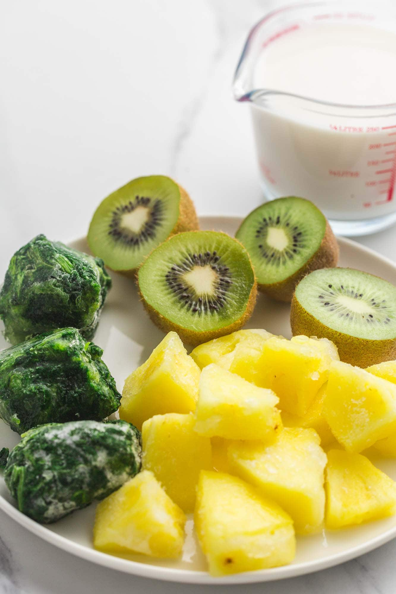 Ingredients needed to make spinach pineapple smoothie: frozen spinach, pineapple, kiwi, and almond milk