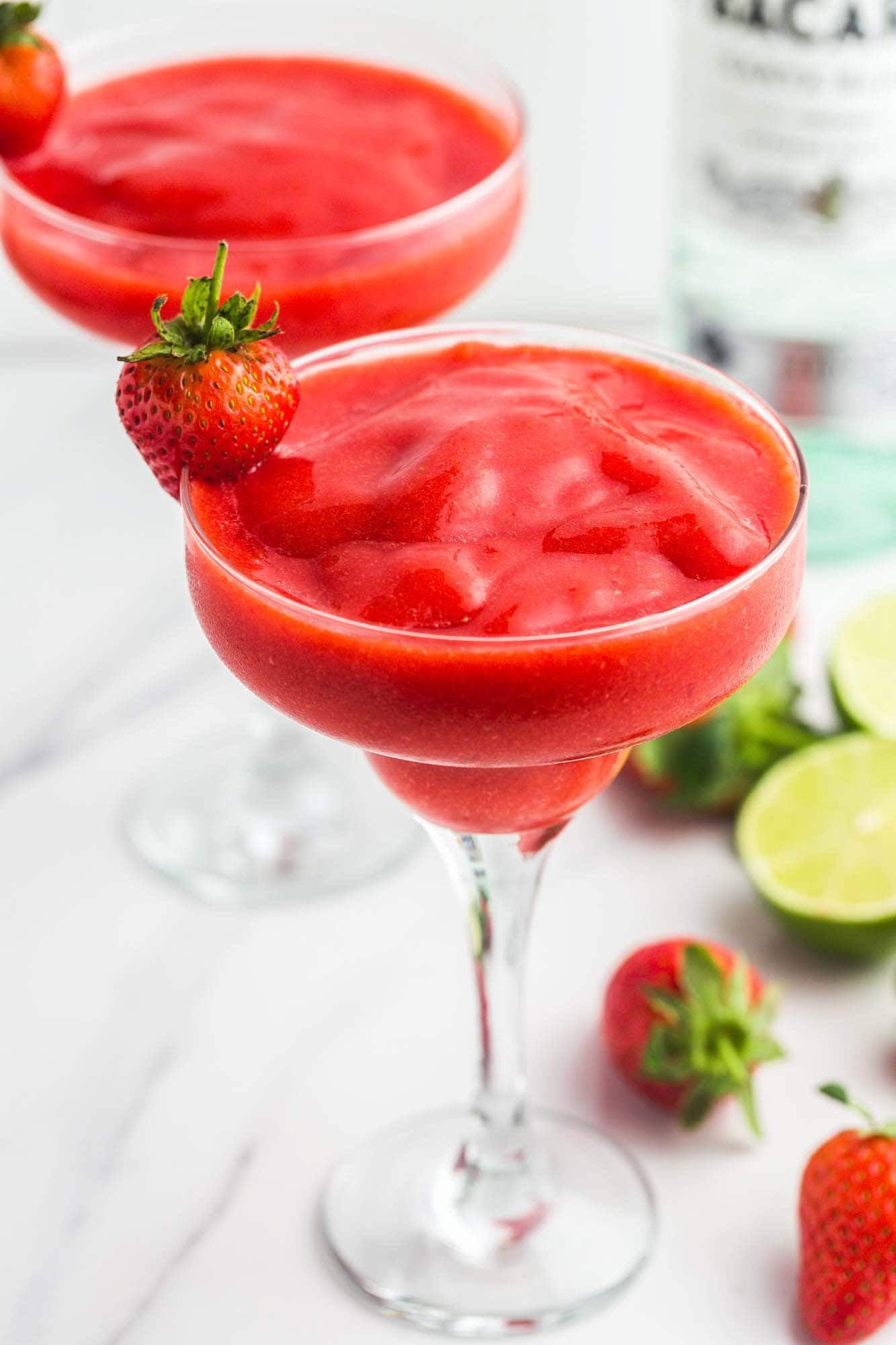 Strawberry Daiquiri in martini glasses, garnished with fresh strawberries. With a bottle of rum, fresh limes, and fresh strawberries in the background.